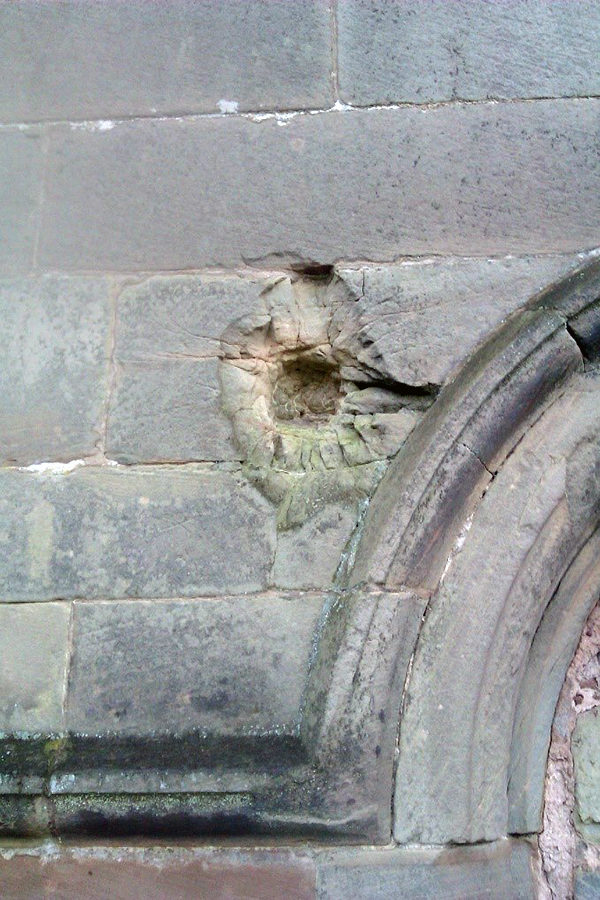 Evidence of the impact of a cannon ball at Tong Castle, Shropshire. Ruins of cottages never rebuilt can be seen nearby.