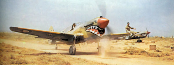 A P-40 Kittyhawk of No. 112 Squadron taxiing through the North African scrub.