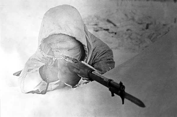 A Finnish soldier wearing improvised winter camouflage takes up a firing position. Winter War